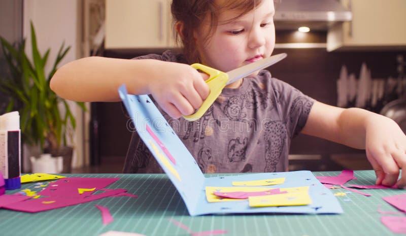 Farbiges Papier des Ausschnitts des kleinen Mädchens mit Scheren stockfotos