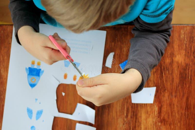 Farbiges Papier des netten Kleinkindausschnitts mit Scheren zu Hause, Draufsicht stockfotos