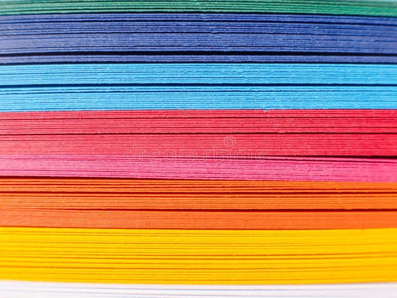 Farbiges Papier, Querschnitt Papierstreifen in den Regenbogenfarben als bunten Hintergrund Das farbige Papier auf einem Hintergru lizenzfreies stockbild