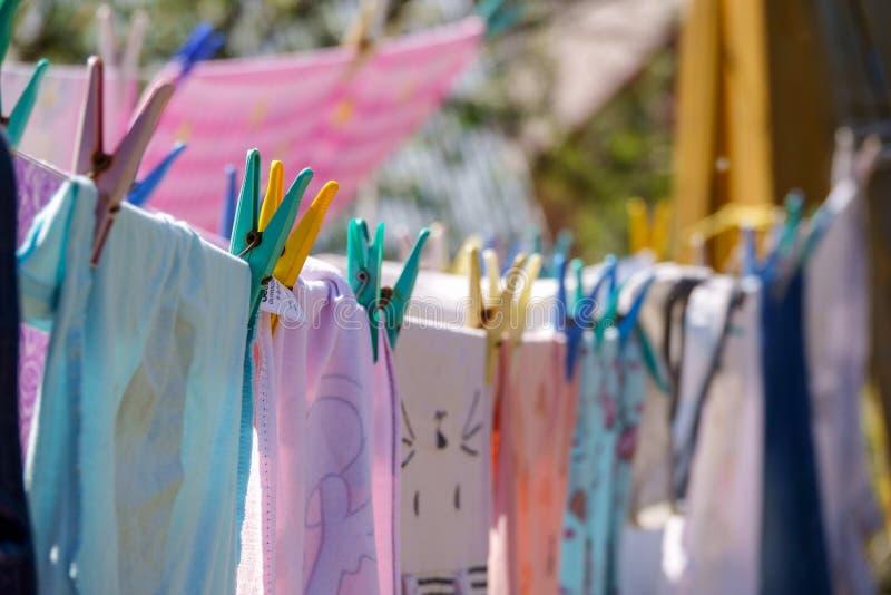 Farbkleidung, die an der Linie im Garten hängt stockbilder