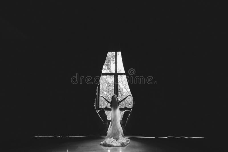 Farblos, Schwarzweißfotografie - die Braut steht mit ihr zurück zu der Kamera und öffnet die Vorhänge in einem großen Raum stockbild
