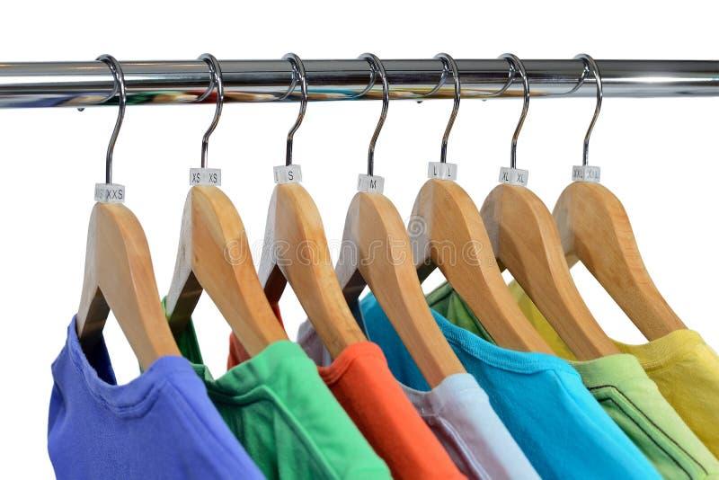 Farbt-shirts hängen am schließenden Gestell, das auf Weiß lokalisiert wird lizenzfreies stockfoto