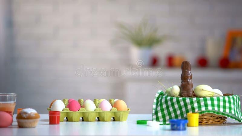 Farbujący jajka w koszu, czekoladowym króliku i farbach na stole, Wielkanocny przygotowanie obrazy stock
