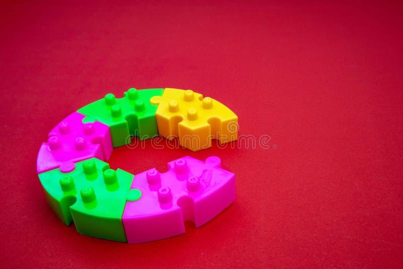 Farbvolles Puzzle auf rotem Hintergrund Zum Üben von Meditation, Problemlösungsfähigkeiten und Geduld Business & Teamwork lizenzfreie stockfotografie