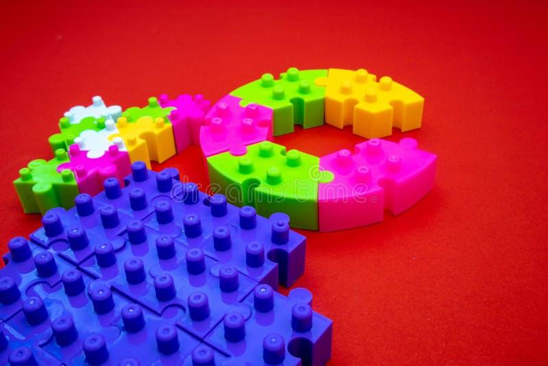 Farbvolles Puzzle auf rotem Hintergrund Zum Üben von Meditation, Problemlösungsfähigkeiten und Geduld Business & Teamwork lizenzfreie stockbilder