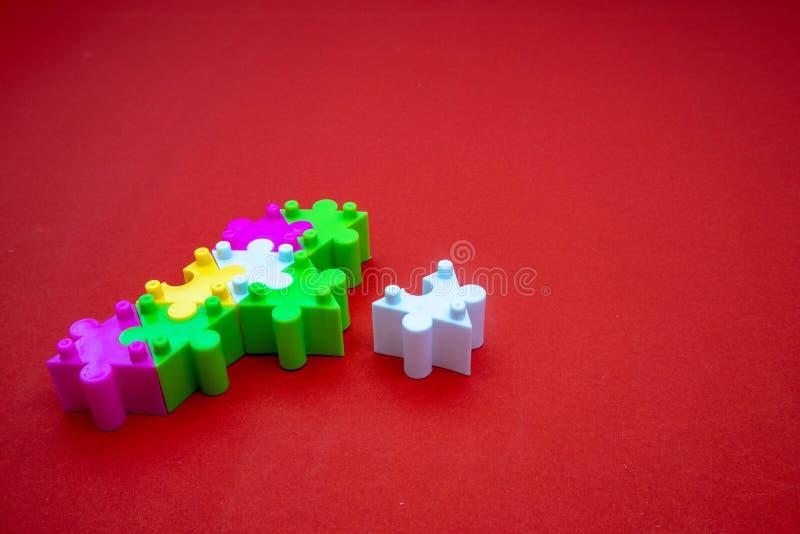 Farbvolles Puzzle auf rotem Hintergrund Zum Üben von Meditation, Problemlösungsfähigkeiten und Geduld Business & Teamwork lizenzfreies stockfoto