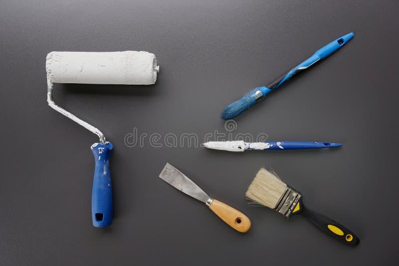 Farby muśnięcia, rolownik i narzędzia dla domowego obrazu na czarnym tle, obrazy stock