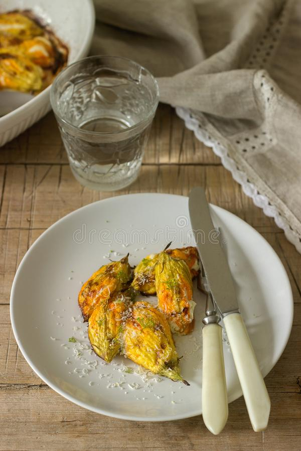 Farcito con i fiori al forno di ricotta e dello zucchini e della zucca del formaggio è servito con un vetro di acqua minerale Sti fotografia stock
