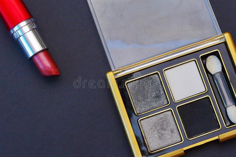 Fard à paupières et rouge à lèvres cosmétiques sur un fond noir image libre de droits