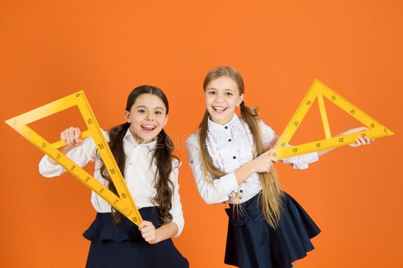 Farda da escola das crianças no fundo alaranjado Meninas bonitos do aluno com réguas grandes Assunto de escola da geometria Tirag fotografia de stock