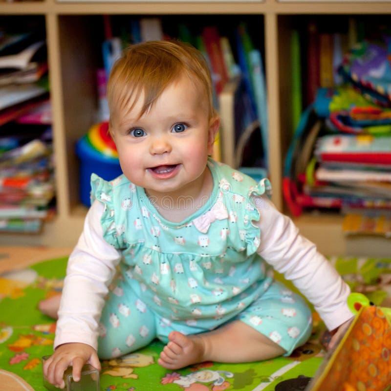 Fare da baby-sitter sorridente sul pavimento in scuola materna fotografia stock