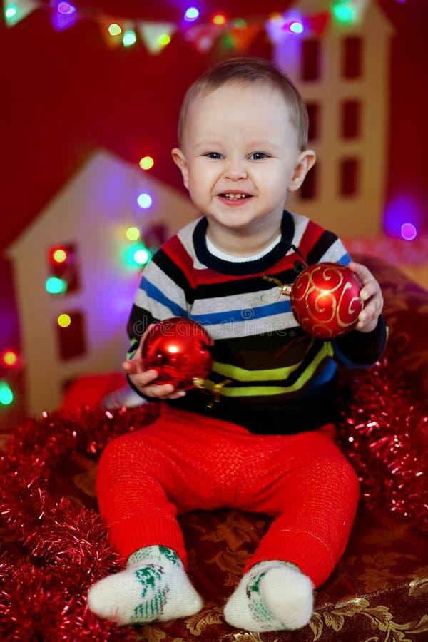 Fare da baby-sitter su fondo di una ghirlanda delle luci e di tenuta delle palle di Natale di un rosso fotografie stock libere da diritti