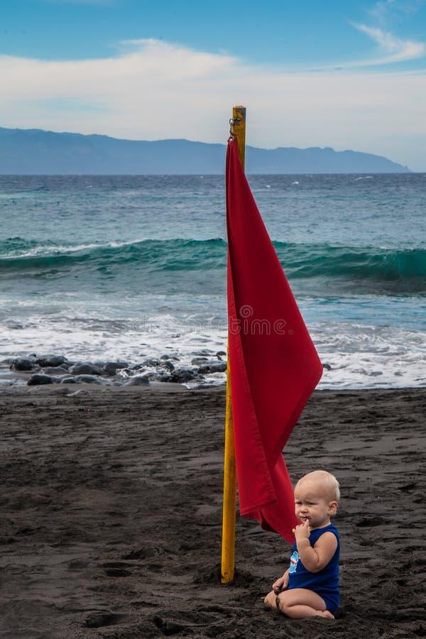 Fare da baby-sitter vicino alla bandiera rossa sulla spiaggia di sabbia vulcanica del nero dell'arena della La di Playa immagini stock libere da diritti
