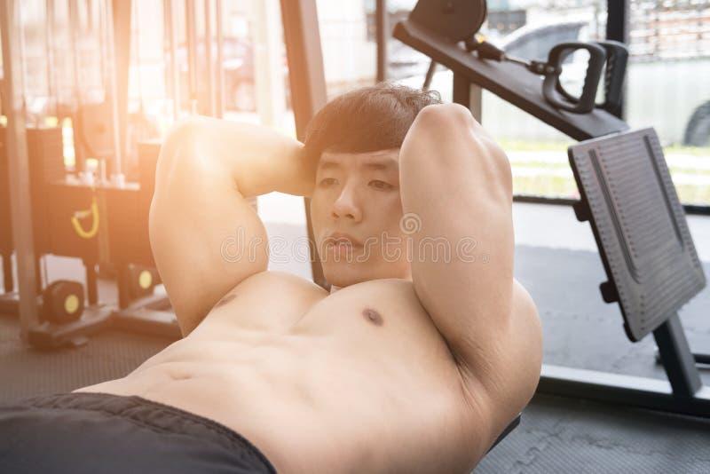 Fare dell'uomo del muscolo si siede su in palestra risolvere maschio del culturista dentro fotografie stock