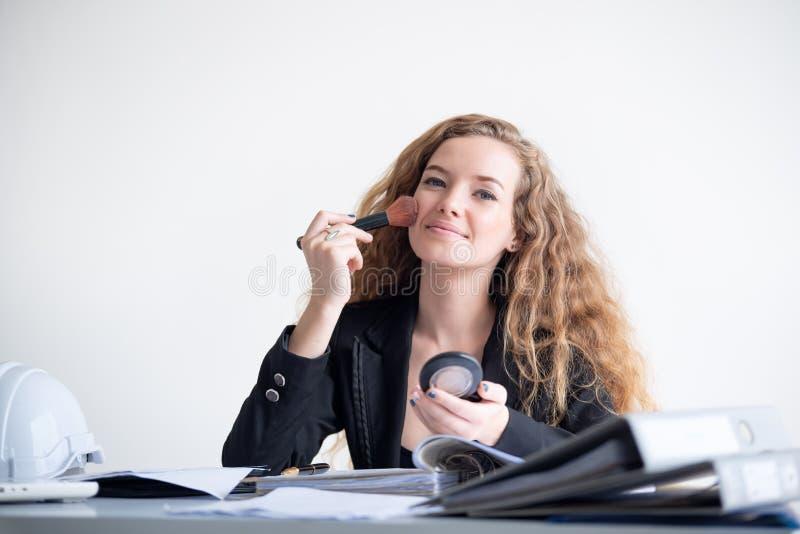 Fare della donna di affari compone al suo ufficio durante il lavoro fotografia stock libera da diritti