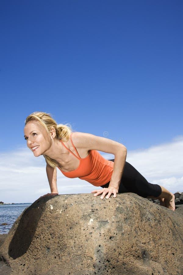 Fare della donna spinge verso l'alto sulla roccia. fotografie stock libere da diritti
