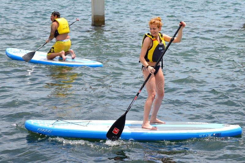 Fare della gente sta sulla pagaia che pratica il surfing, o imbarcante (SUP), ai giochi estremi di Barcellona di sport di LKXA immagini stock libere da diritti