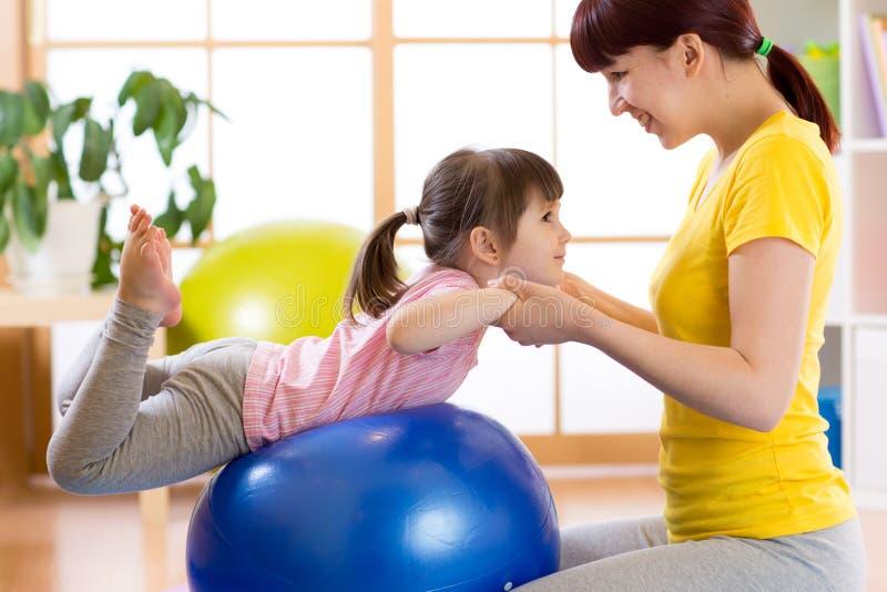 Fare della ragazza del bambino relativo alla ginnastica sulla palla di forma fisica con la madre a casa fotografia stock libera da diritti