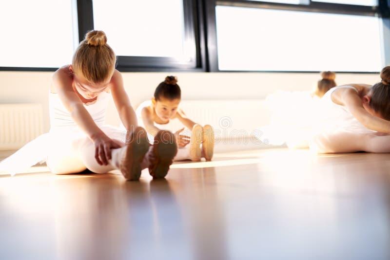 Fare delle ragazze di balletto si siede e raggiunge l'esercizio di riscaldamento fotografia stock libera da diritti