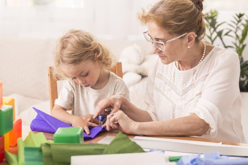 Fare gli artigianato con la babysitter fotografia stock libera da diritti