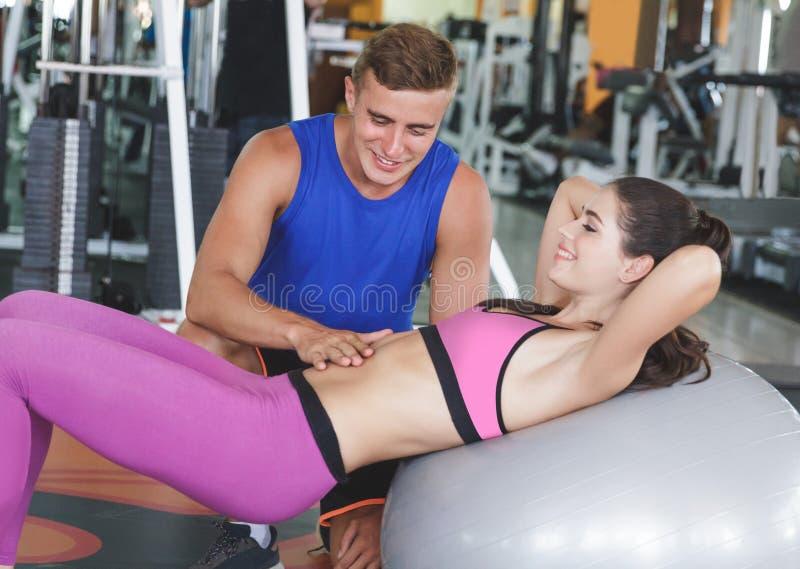 Fare grazioso della giovane donna si siede su sulla palla di esercizio con il suo amico immagine stock libera da diritti
