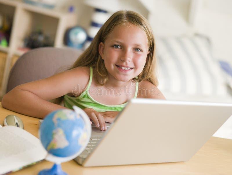 fare i giovani del computer portatile di lavoro della ragazza immagine stock libera da diritti