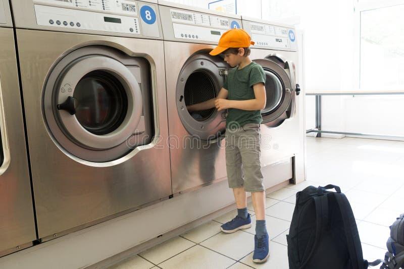 Fare la lavanderia in un salone della lavanderia automatica immagini stock libere da diritti