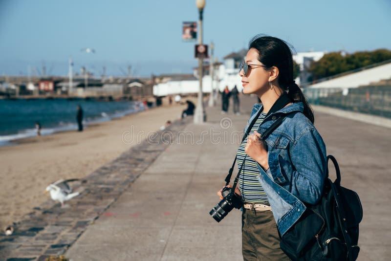 Fare un giro turistico sorridente della macchina fotografica della tenuta dell'uomo della lente della donna fotografie stock