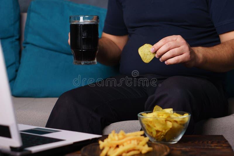 Fare un spuntino irragionevole, mangiante troppo, mancanza di attività fisica fotografie stock