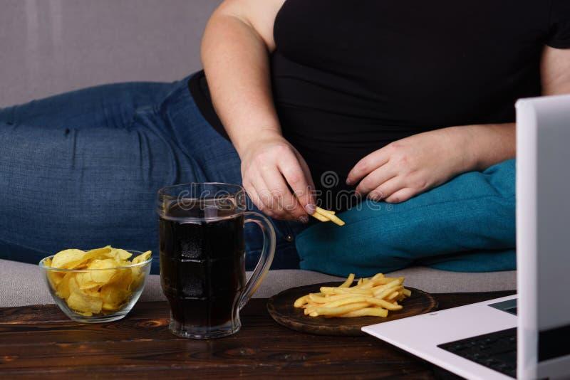 Fare un spuntino irragionevole, mangiante troppo, mancanza di attività fisica fotografia stock libera da diritti
