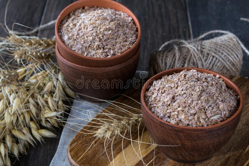 Farelo do trigo, da aveia na bacia da argila e orelhas do trigo e da aveia Suplemento dietético para melhorar a digestão imagem de stock