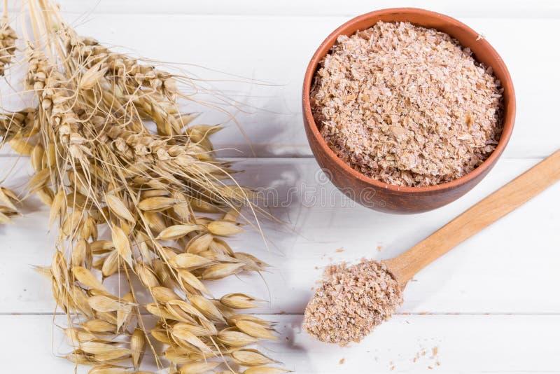Farelo do trigo, da aveia na bacia da argila e orelhas do trigo e da aveia Suplemento dietético para melhorar a digestão foto de stock royalty free