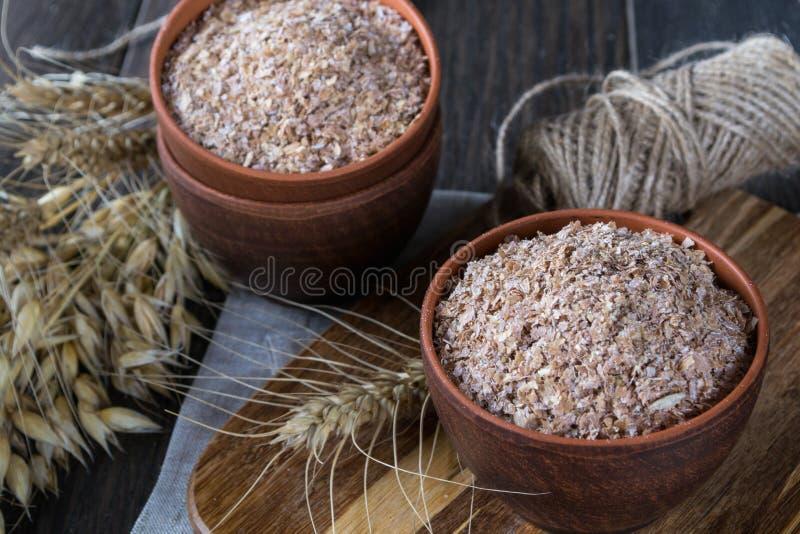 Farelo do trigo, da aveia na bacia da argila e orelhas do trigo e da aveia Suplemento dietético para melhorar a digestão fotografia de stock royalty free