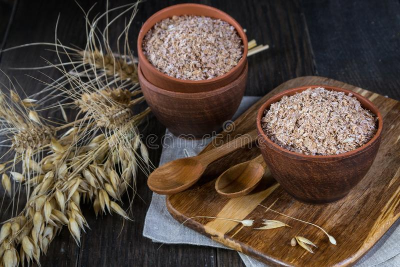 Farelo do trigo, da aveia na bacia da argila e orelhas do trigo e da aveia Suplemento dietético para melhorar a digestão foto de stock