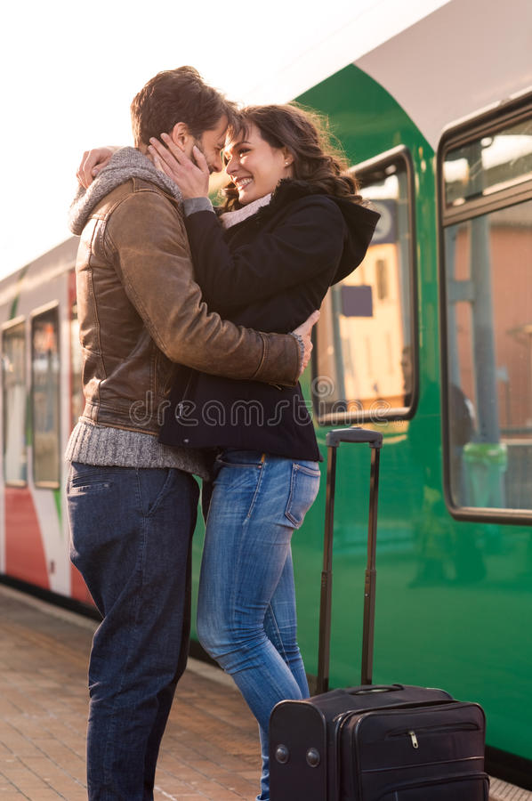 Farewell at train station. Happy couple embracing on railway station platform stock images