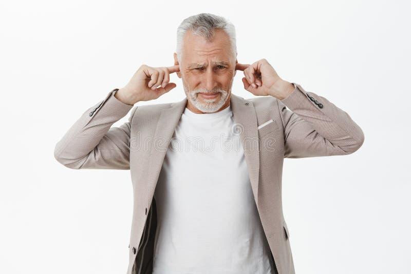 Farfadern kan inte använda sonsonen som spelar valsar som täcker öron med pekfingrar från att reagera för obehag som är negativt  royaltyfria bilder