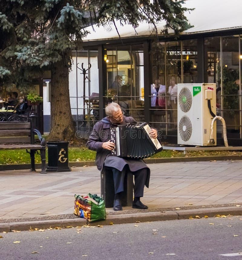 Farfadern med ett dragspel sitter och spelar Ryssland, Krasnodar, oktober 7,2018 royaltyfria bilder