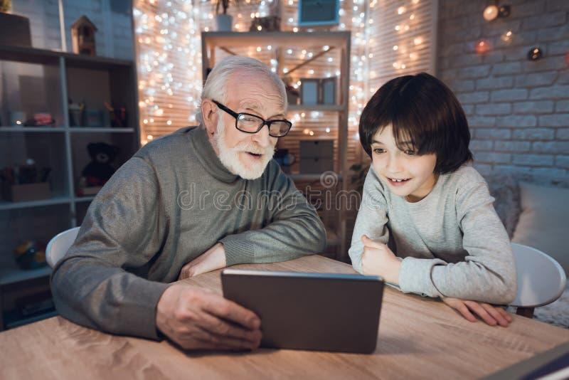 Farfadern och sonsonen håller ögonen på film på minnestavlan på natten hemma royaltyfria bilder