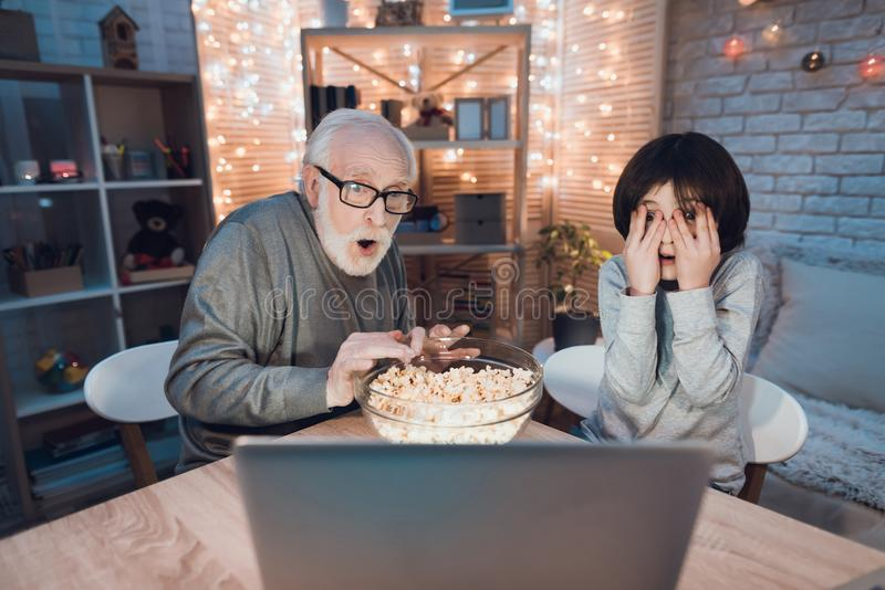 Farfadern och sonsonen håller ögonen på läskig film på natten hemma royaltyfria bilder