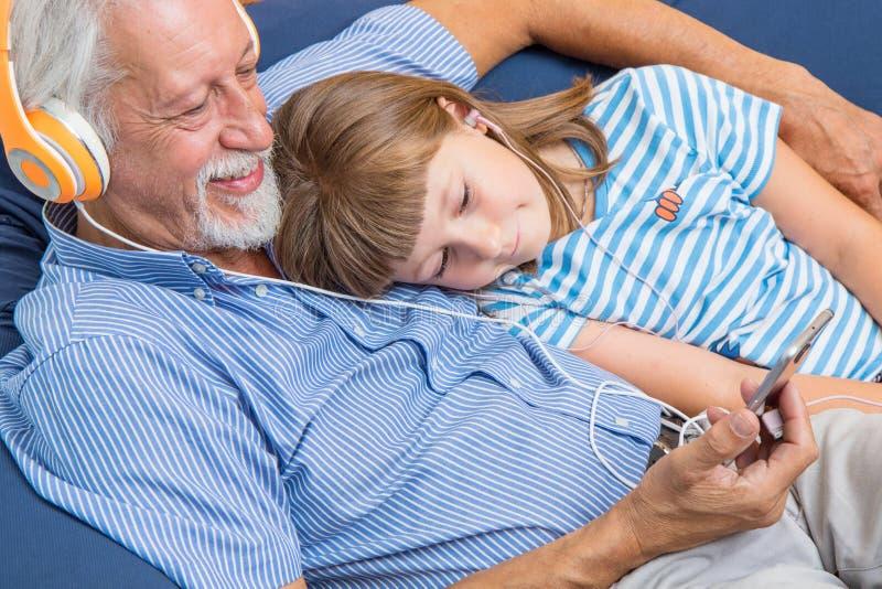 Farfadern och sonsonen med hörlurar lyssnar till musik som kramar sig på soffan royaltyfri foto