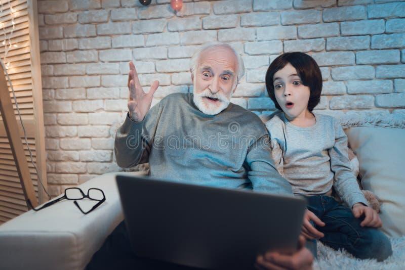 Farfadern och sonsonen sitter hållande ögonen på intressant film på natten hemma arkivbilder