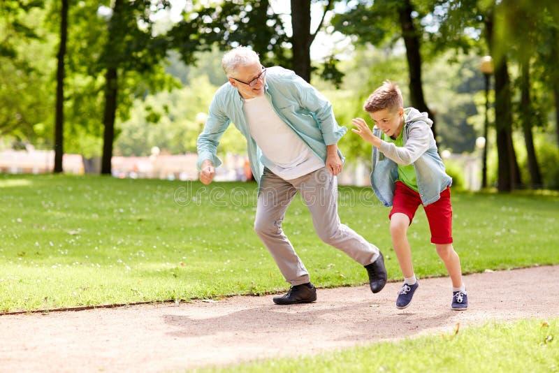 Farfadern och sonsonen som springer på sommar, parkerar arkivfoton