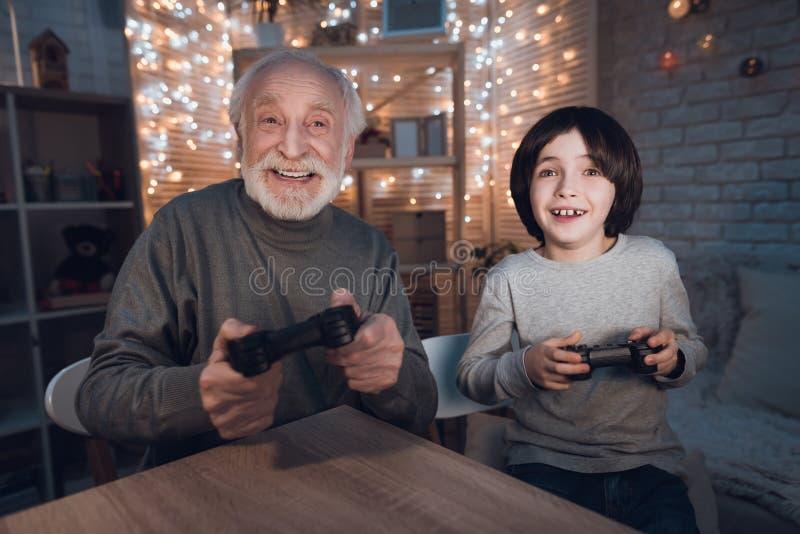 Farfadern och sonsonen spelar videospel på natten hemma arkivbild