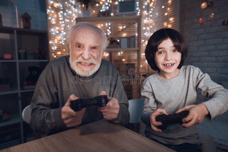 Farfadern och sonsonen spelar videospel på natten hemma royaltyfri fotografi