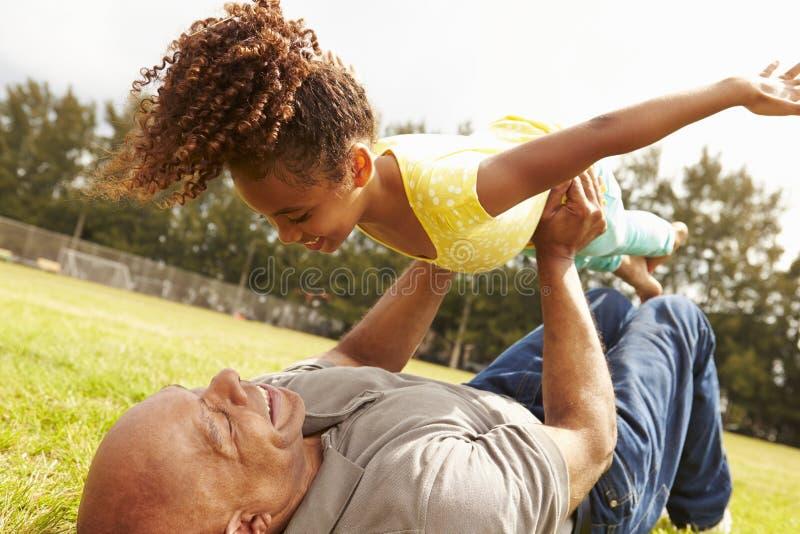 Farfadern som spelar leken med sondottern parkerar in arkivbilder