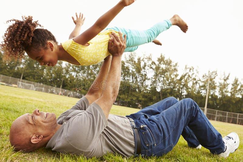 Farfadern som spelar leken med sondottern parkerar in fotografering för bildbyråer