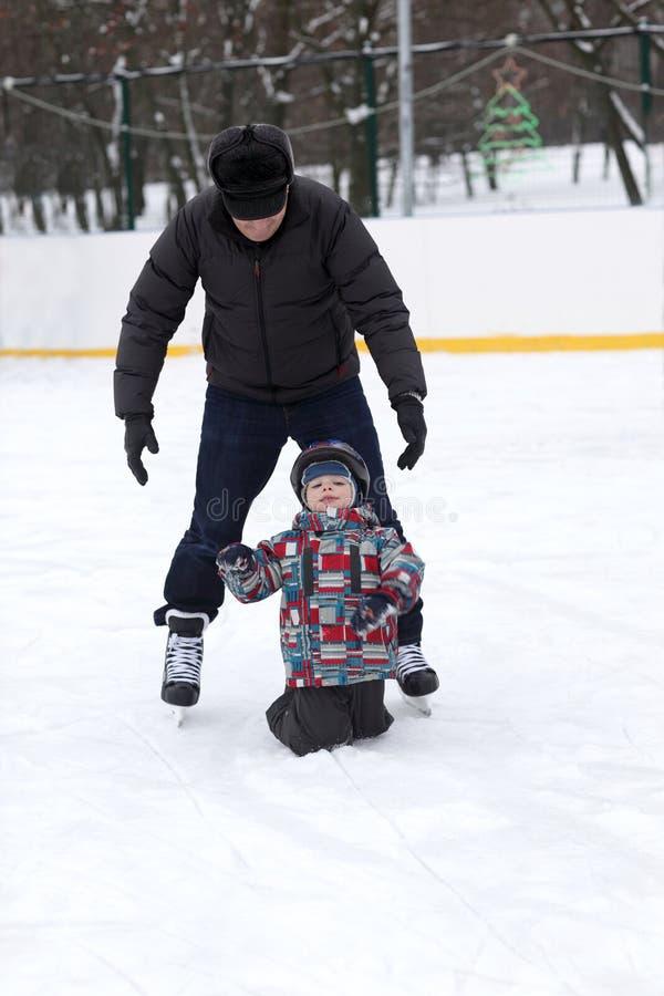 Farfadern undervisar hans barnbarn att åka skridskor arkivfoton