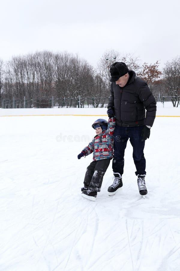 Farfadern undervisar hans sonson att åka skridskor arkivfoto