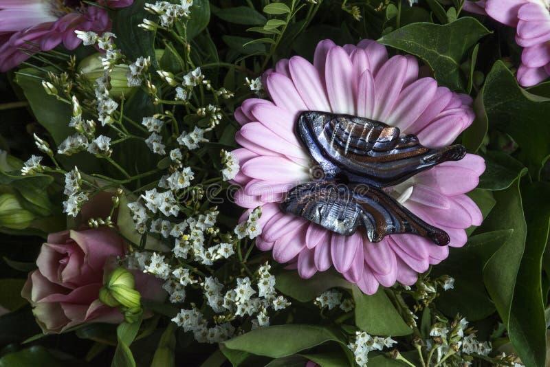 Farfalla artificiale di vetro sul fiore e sulle foglie rosa fotografia stock libera da diritti