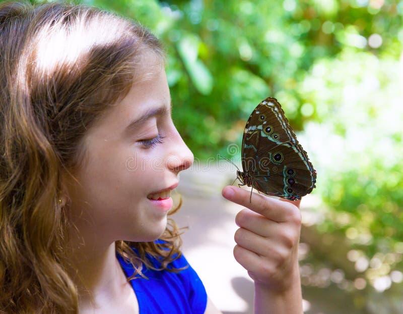 Farfalla blu Peleides di Monrpho del dito della tenuta della ragazza fotografia stock libera da diritti